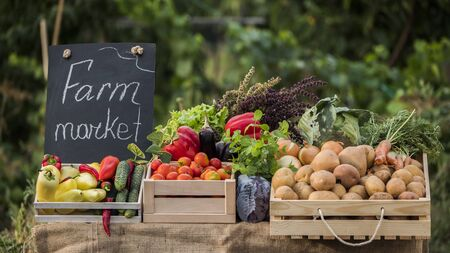 A counter with fresh vegetables at a farmers market. Vegetables from local producers
