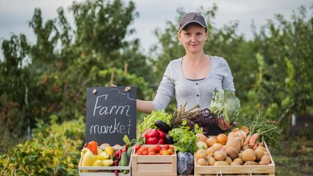 Portrait of a farmer woman selling vegetables at a farmers market Imagens