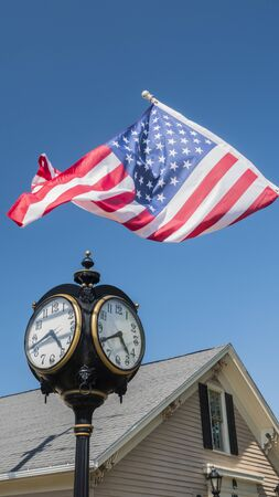 Antique clock on a pillar, a wooden house in the background and the USA flag - American outback concept