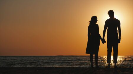 Silhouettes of a young couple in love standing near the sea at sunset
