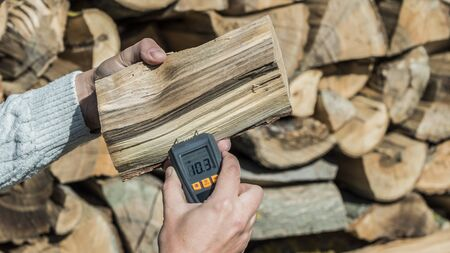 A man measures the humidity of firewood with a moisture meter, monitoring fuel quality