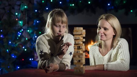 Mom and daughter play a board game with wooden blocks Stock fotó