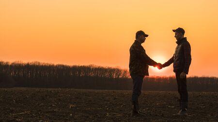 Two farmers shaking hands on a plowed field Reklamní fotografie