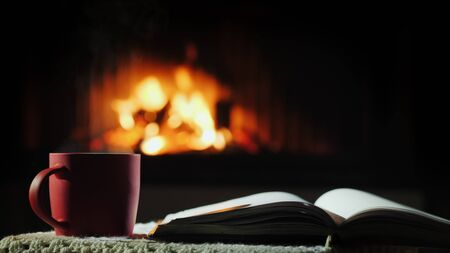 An open book and a cup of hot tea on the background of the fireplace where the fire is burning Stockfoto