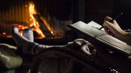 A man begins to write on a blank page of a notebook, sits by the fireplace