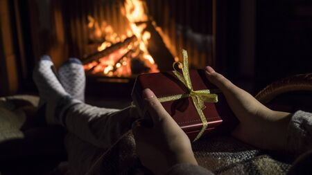 Woman holds a box with a gift in her hands, sits near the fireplace