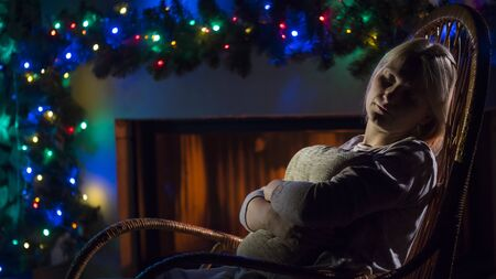 A young woman sleeps in a rocking chair by the fireplace. Room decorated with Christmas garlands