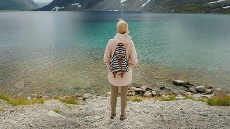 A woman admires a beautiful high mountain lake in the mountains of Norway. The sky and mountains are reflected in the water - a beautiful sight. 4k video