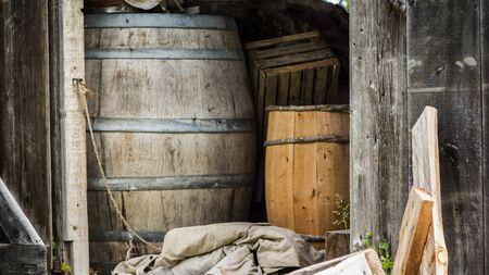 Several old barrels in a rural barn. Vintage Farm Landscape.