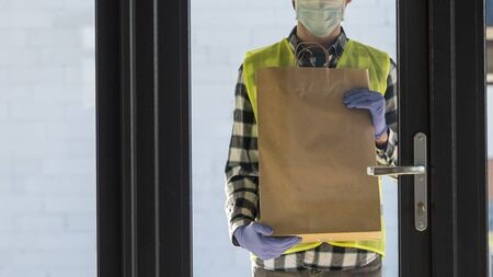 Delivery of food in quarantine, courier with a package stands at the door of the house Standard-Bild