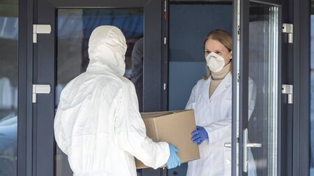 A person in a protective suit is handed a box of medicines to a doctor at the entrance to the hospital