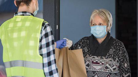 Courier brings food bags to elderly womans home 写真素材