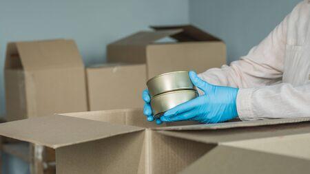 Volunteer packs canned goods in a cardboard box, prepares food kits