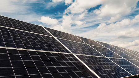 Clouds float quickly over solar power plant panels.