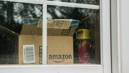 Wilson, NY, USA, July 2019: An open box from the parcel with the Amazon logo is visible outside the window.