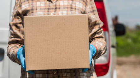 Courier with cardboard box in hand stands against the background of the delivery service van