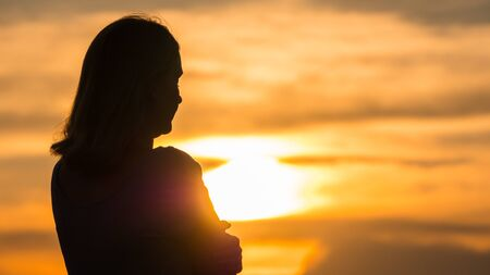 Silhouette of a young pensive woman at sunset looking into the distance.