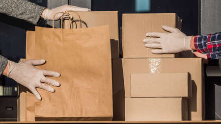 Couriers in protective gloves put parcels on the doorstep of the house 写真素材
