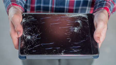 A man holds a tablet with a broken screen 写真素材