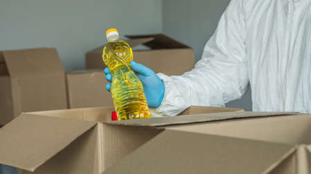 A man in protective clothing puts a bottle of vegetable oil in a drawer, completes a food set 写真素材