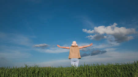 A woman stands on a green meadow against a beautiful blue sky with clouds. Wide angle shot