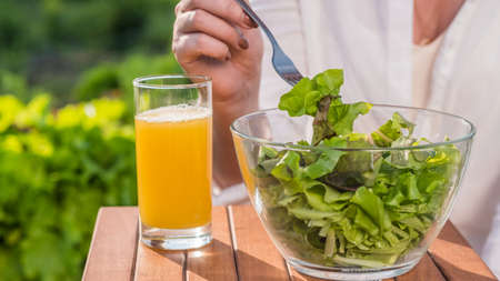 A woman eats salad in nature, next to a glass of juice. Healthy eating 写真素材