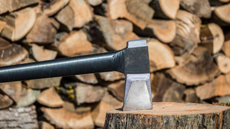 Modern ax for harvesting firewood on the background of woodpile