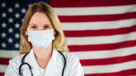 Woman doctor in mask against the background of the American flag