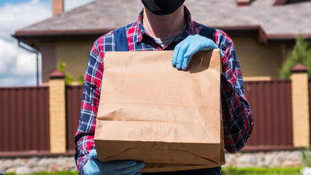 The messenger in gloves and mask holds a bag with groceries