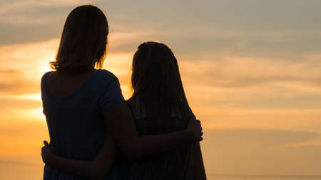 Silhouettes of mother and daughter at sunset