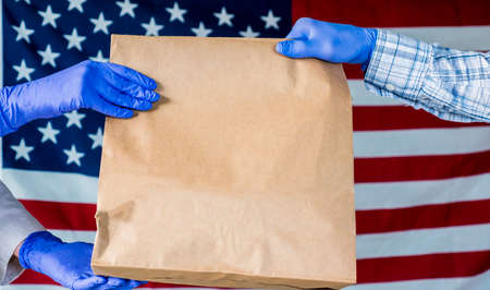Messenger in gloves pass the parcel into the hands of the recipient against the background of the American flag