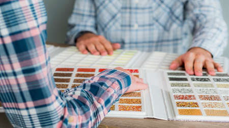A group of designers are working on a color solution, using a catalogue of samples