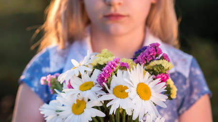 Blonde girl holds a bouquet of flowers, stands in a meadow at sunset. Closeup shot