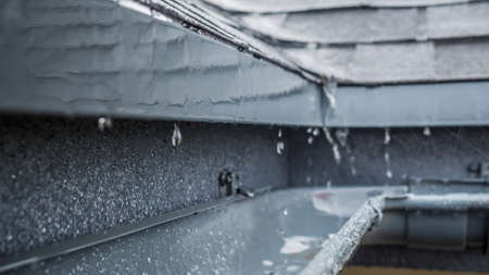 Jets of rain drain into the drainage system on the roof of the house