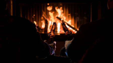 Winter escape - friends relax by the fireplace with beer in their hands 写真素材
