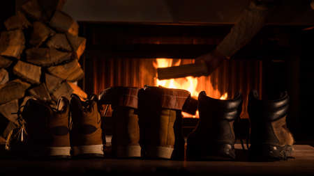 Shoes are drying by the fireplace, in the background a man throws firewood into a firebox