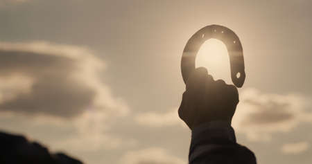 Hand of a man with a horseshoe against the sky and the sun Reklamní fotografie