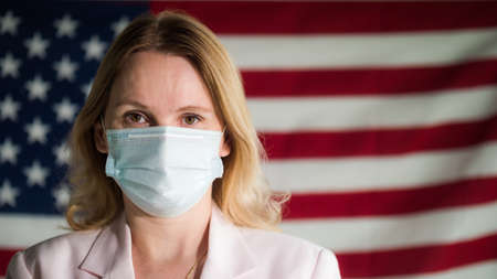 Portrait of a woman of a businessman in a protective mask against the background of the U.S. flag Фото со стока