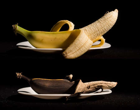 Composition Two bananas in plates - fresh and rotten Reklamní fotografie