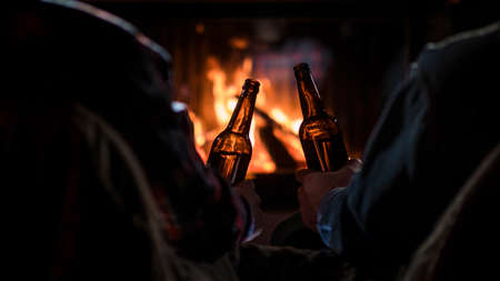 Two men rest with bottles of beer in hand by the fireplace