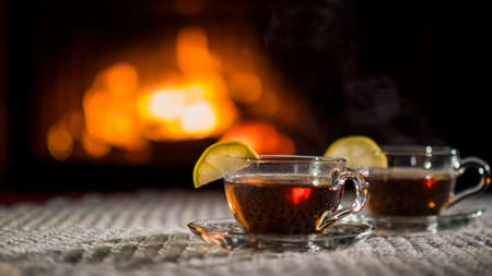 Two cups of tea with lemon on the background of the fireplace. Stand on a white knitted tablecloth