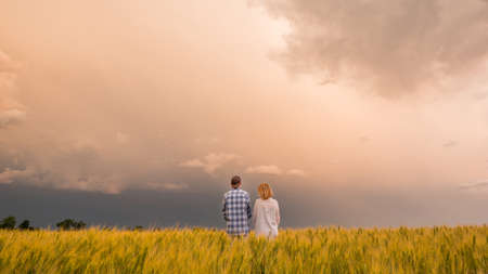 A man and a woman stand in a field of wheat against a dramatic sky before a thunderstorm