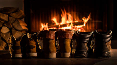 A few pairs of winter shoes are drying near the fireplace where the fire is on Reklamní fotografie