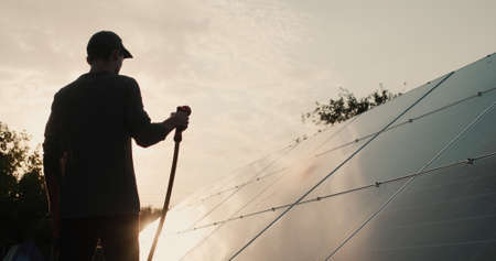 Silhouette of a man washing a solar power plant panel Archivio Fotografico