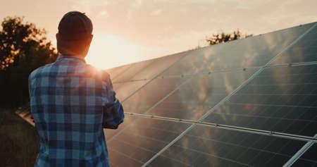 Owner looks at solar power plant panels at sunset Reklamní fotografie