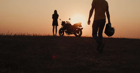 The silhouette of a man walking to the motorcycle where he is waiting for a young woman. Romantic travel concept