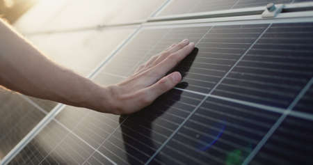 Mens hand strokes the surface of solar panels