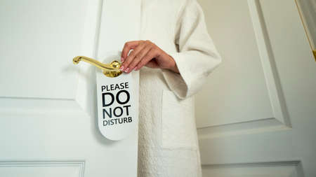 A mans hand hangs a sign on the door of the hotel room with a request not to disturb Фото со стока