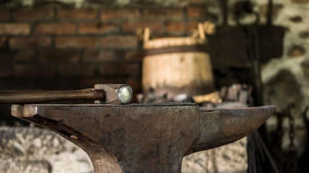 Equipment of the old forge - anvil and hammer, in the background a wooden bucket