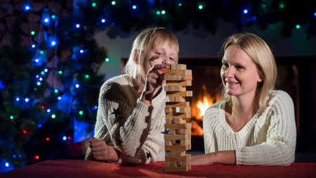 Mom and daughter play a board game with wooden blocks Reklamní fotografie